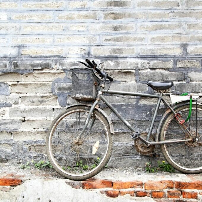 Lonely vintage bicycle near old brick wall